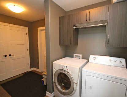Laundry cabinets with drying rod by Hiebert Cabinets in Bow Island, Alberta.. Laundry | Other | Contemporary
