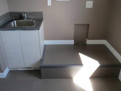 Slab doors in a laundry room by Hiebert Cabinets in Bow Island, Alberta.. Laundry | Other | Contemporary