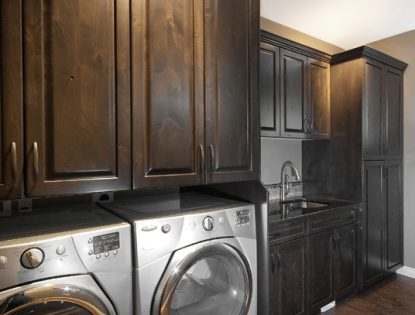 Washer and dryer on custom platform by Hiebert Cabinets in Bow Island, Alberta.. Laundry | Alder | Rustic | Raised Panel