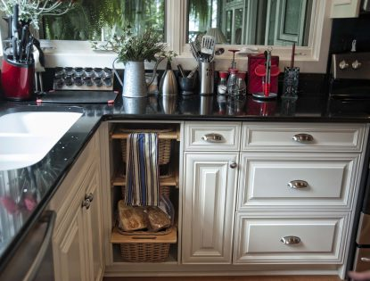 Potato and onion pullout built into cabinetry by Hiebert Cabinets in Bow Island, Alberta.. Kitchen | Painted | Raised Panel | Mitered Doors | Unique Feature