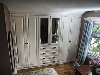 Bedroom cabinetry with mirror inserts by Hiebert Cabinets in Bow Island, Alberta.. Closet | Painted | Mitered Doors | Raised Panel | Traditional