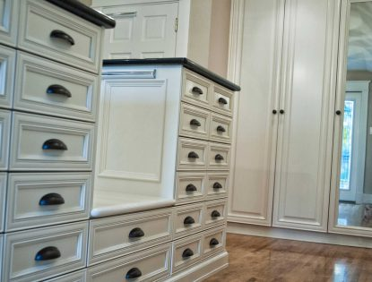 White closet cabinets with black cup pulls by Hiebert Cabinets in Bow Island, Alberta.. Closet | Painted | Mitered Doors | Traditional