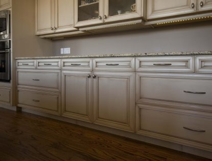 Cream painted kitchen cabinets with antique finish by Hiebert Cabinets in Bow Island, Alberta.. Kitchen | Painted | Dusted | Raised Panel | Mitered Doors | Traditional