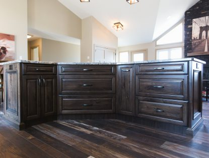 Dark dusted cabinet finish with curved handles by Hiebert Cabinets in Bow Island, Alberta.. Kitchen | Walnut | Dusted | Islands | Raised Panel | Traditional