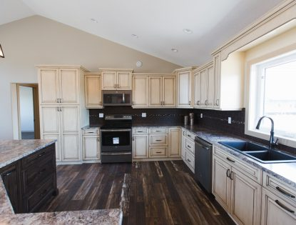 Two toned kitchen featuring curved island by Hiebert Cabinets in Bow Island, Alberta.. Kitchen | Walnut | Dusted | Painted | Distressed | Islands | Raised Panel | Traditional