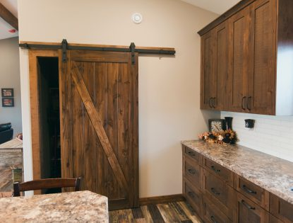 A Sliding Barn door by Hiebert Cabinets in Bow Island, Alberta.. Kitchen | Alder | Rustic | Flat Panel | Unique Feature