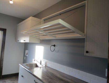 Tip down drying rod by Hiebert Cabinets in Bow Island, Alberta.. Laundry | Other | Unique Feature