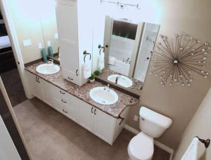 Double sink bathroom with custom vanity tower by Hiebert Cabinets in Bow Island, Alberta.. Bathroom | Painted | Contemporary | Flat Panel